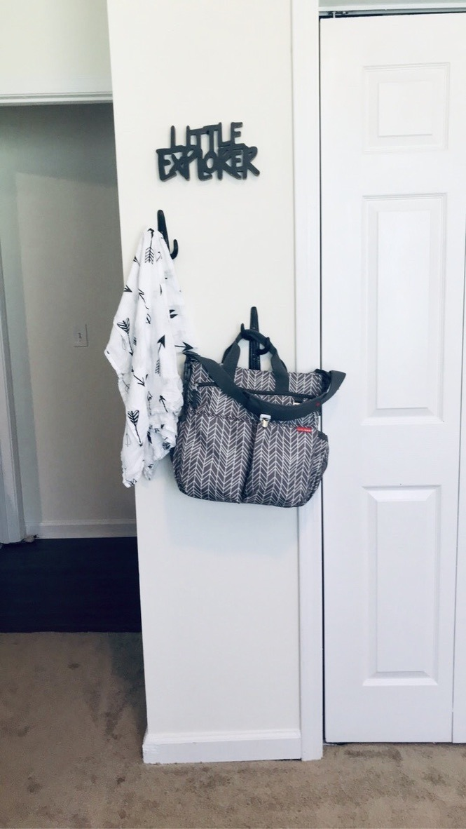 Wall decor including a baby diaper bag, cactus hooks, little explorer sign, and arrow patterned swaddle. BOY NURSERY TOUR 2020