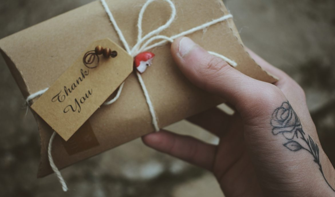 A thank you note attached to a gift with a string around it.