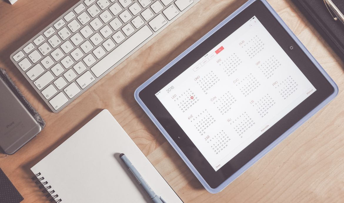 This picture is an ipad showing a calendar, notebook, phone, and a keypad on a desk.