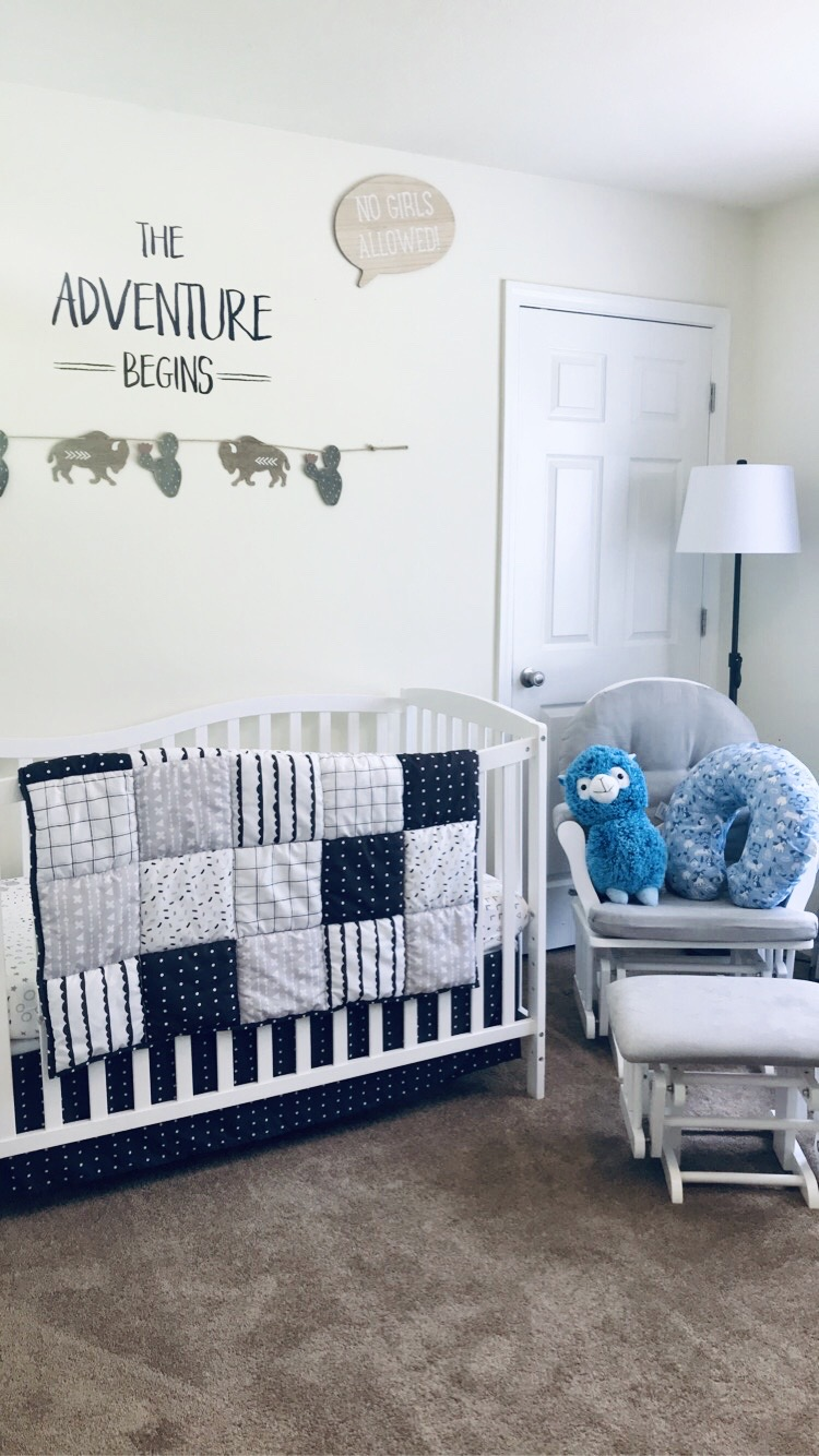 Crib with patterned blanket on top. Also a blue lama and blue boppy pillow. The adventure begins sign on the wall as well as a no girls allowed sign. A wall hanger of cactus and buffalo. BOY NURSERY TOUR 2020
