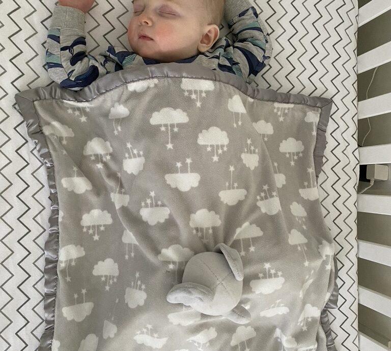 Sebastian in the crib with an elephant blanket.